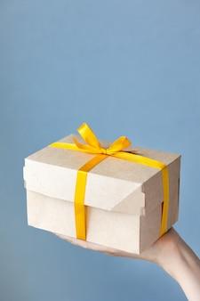 Mano de mujer sosteniendo una caja de cartón kraft color natural mujer sosteniendo cajas con cinta de regalo amarilla