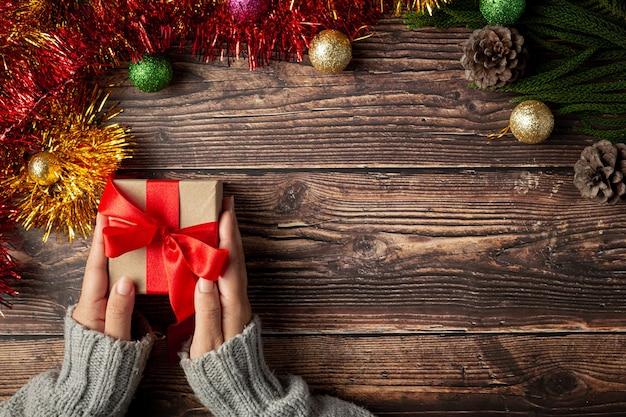 Mano de mujer sosteniendo una caja de regalo con cinta roja sobre un piso de madera