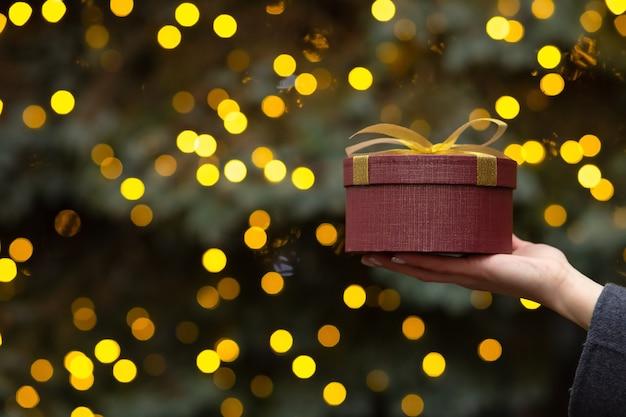 Mano de mujer sosteniendo una caja de regalo redonda con un lazo en el fondo del árbol de navidad y luces borrosas. espacio vacio