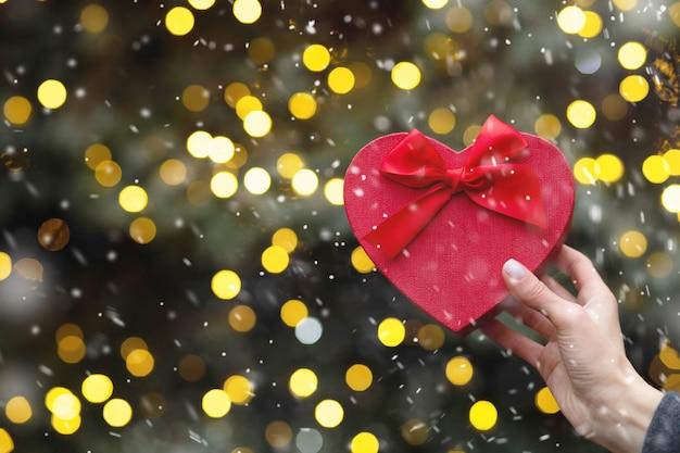 Mano de mujer sosteniendo una caja de regalo roja en forma de corazón durante las nevadas. espacio vacio
