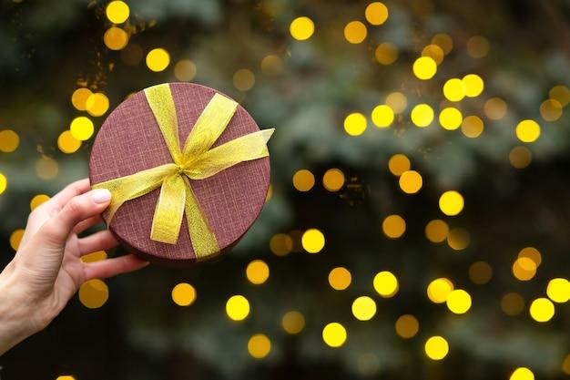 Mano de mujer sosteniendo una caja de regalo roja con un lazo en el fondo del árbol de navidad y luces borrosas. espacio vacio