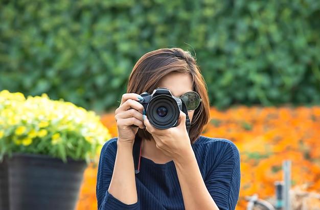 Mano mujer sosteniendo la cámara tomando fotos fondo de árboles y flores