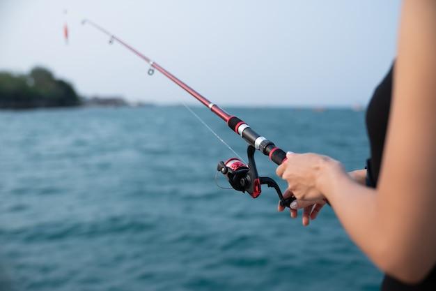 Mano de mujer sosteniendo caña de pescar con mar, pesca al atardecer.