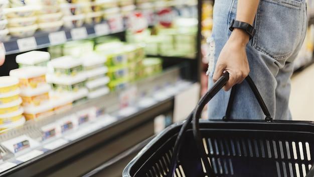 Mano de mujer sosteniendo la cesta de la compra vacía