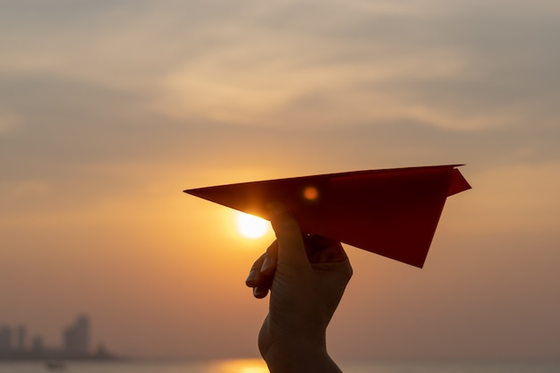 Mano de mujer sosteniendo cohete de papel naranja con durante la puesta del sol