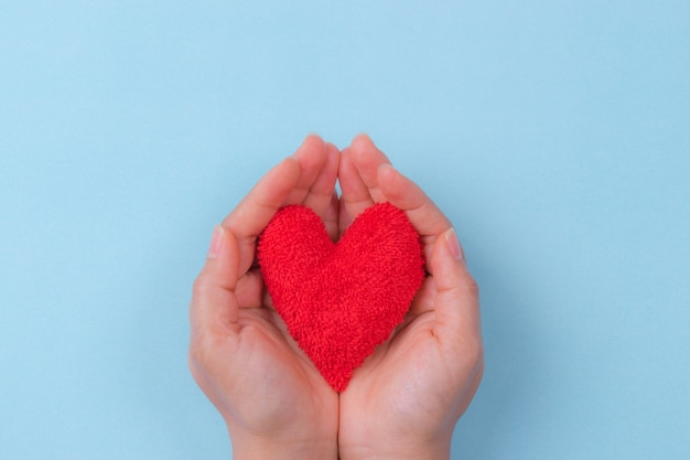 Mano de mujer sosteniendo un corazón rojo. día mundial del corazón.