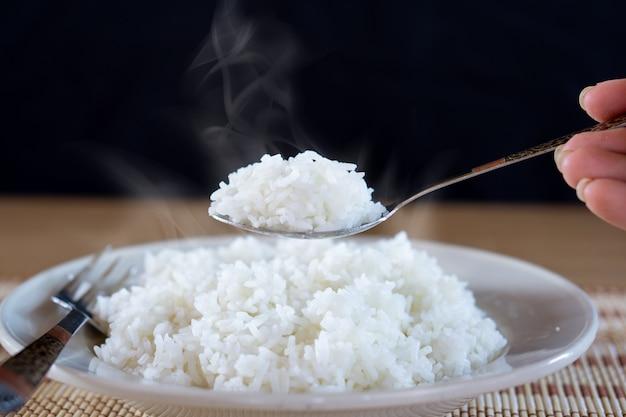 Mano de mujer sosteniendo una cuchara comiendo arroz caliente