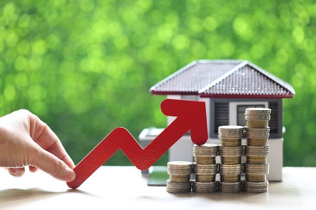 Mano de mujer sosteniendo gráfico de flecha roja y pila de monedas dinero con casa modelo sobre fondo verde natural
