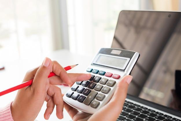 Mano de mujer sosteniendo el lápiz rojo y trabajando con la calculadora,