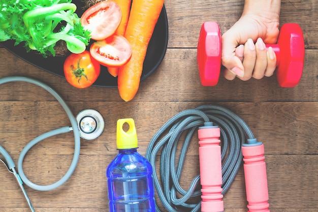 Mano de mujer sosteniendo mancuernas, alimentos saludables y equipos de fitness en madera