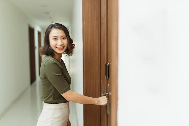 Mano de mujer sosteniendo las manijas de las puertas modernas cerradura electrónica abrir la puerta del apartamento