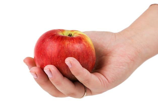 Mano de mujer sosteniendo manzana roja aislado sobre un fondo blanco.