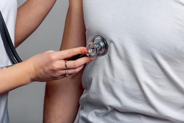 Mano de mujer sosteniendo el pecho del estetoscopio masculino en camiseta blanca y examinándolo.
