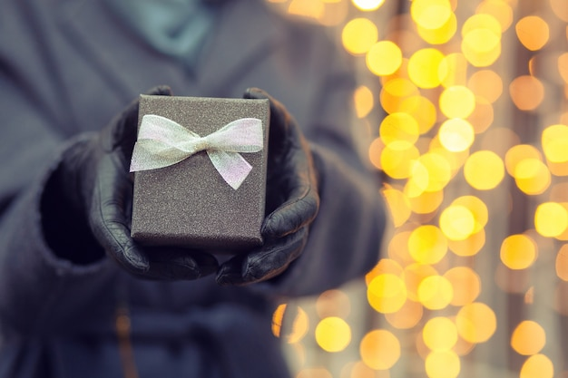 Mano de mujer sosteniendo una pequeña caja de regalo con un lazo en el fondo de luces borrosas de navidad. espacio vacio