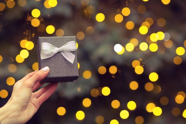 Mano de mujer sosteniendo una pequeña caja de regalo plateada con un lazo en el fondo del árbol de navidad y luces borrosas. espacio vacio