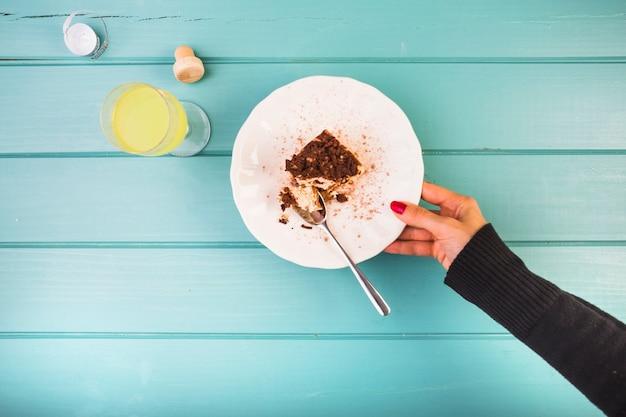 Mano de mujer sosteniendo la placa de pastelería con bebida en la mesa