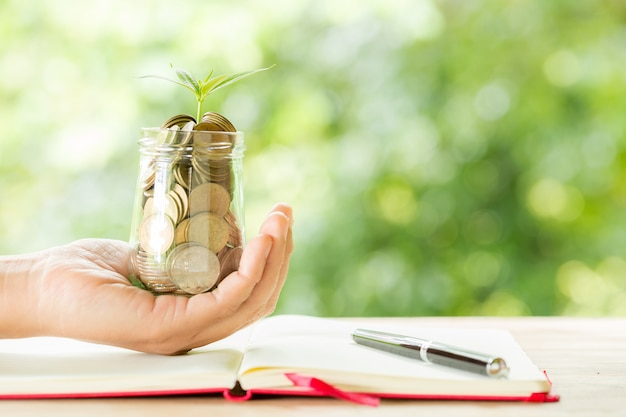 Mano de mujer sosteniendo la planta que crece de la botella de monedas