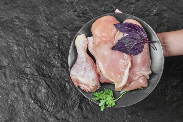 Mano de mujer sosteniendo un plato de partes de pollo crudo con albahaca sobre una superficie oscura