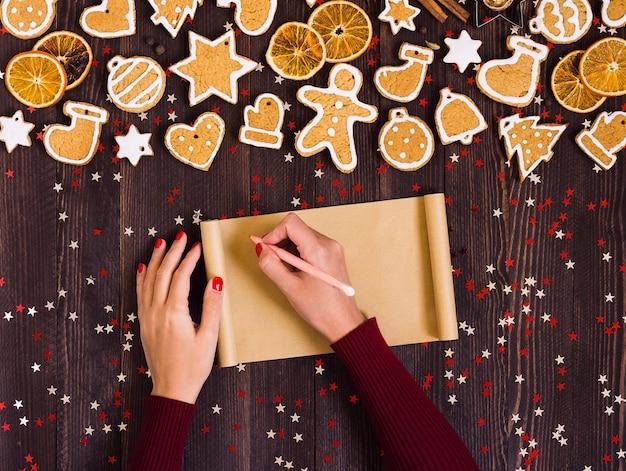 Mano de mujer sosteniendo una pluma de papel vacío para hornear pan de jengibre de navidad de receta