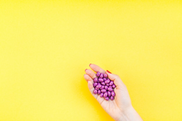 Mano de mujer sosteniendo puñado de pastillas de color púrpura