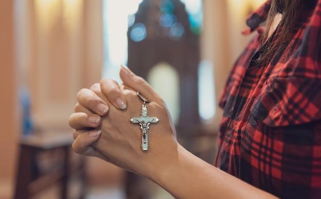 Mano de mujer sosteniendo el rosario contra la cruz y rezando a dios en la iglesia.