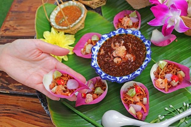 Mano de mujer sosteniendo un sabroso pétalo de loto fresco envuelto llamado miang kham en idioma tailandés