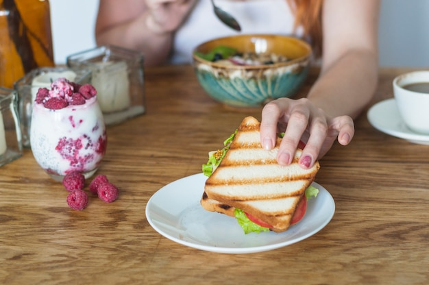 Mano de mujer sosteniendo sandwich de plato blanco en mesa de madera