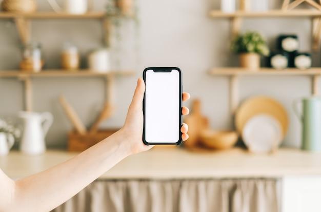 Mano de mujer sosteniendo smartphone con pantalla blanca vertical en la cocina