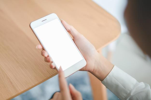 Mano de mujer sosteniendo smartphone con pantalla en blanco en la mesa de café.