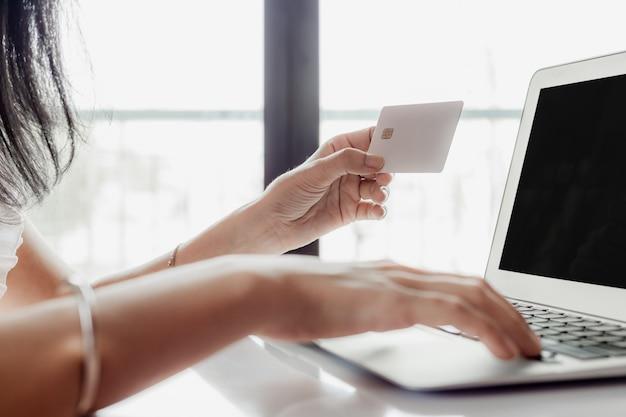 Mano de mujer sosteniendo una tarjeta de crédito y usando la computadora para compras en línea y pago