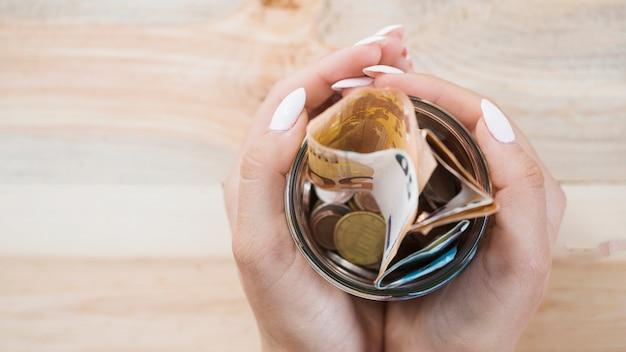 Mano de mujer sosteniendo el tarro de cristal con billetes y monedas de euro sobre fondo de madera