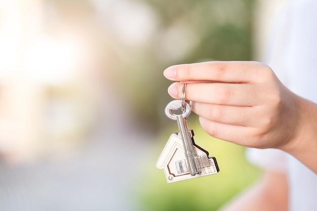 Mano de mujer sosteniendo la tecla de inicio. concepto de negocio de bienes raíces.