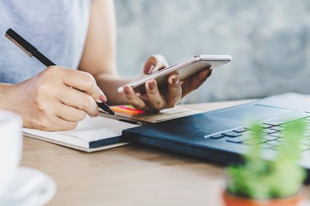 Mano de mujer sosteniendo teléfono inteligente y escribir