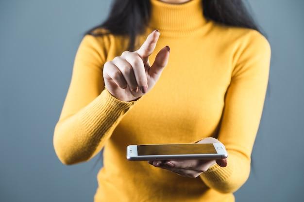 Mano de mujer sosteniendo teléfono inteligente sobre fondo gris