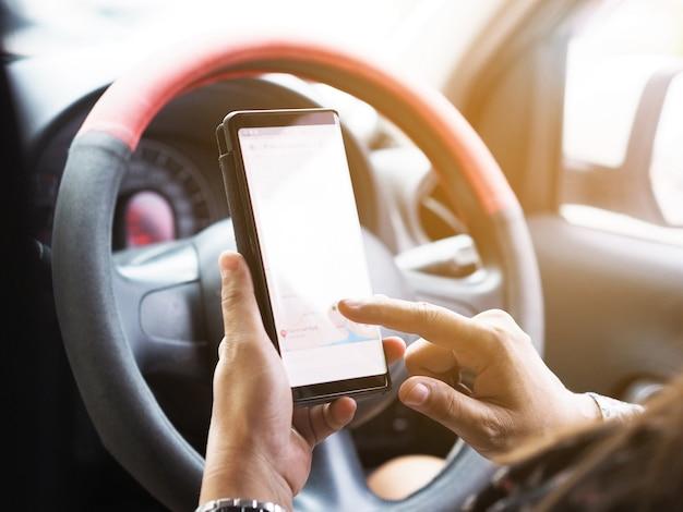 Mano de mujer sosteniendo el teléfono móvil y apuntando la pantalla táctil durante la conducción.
