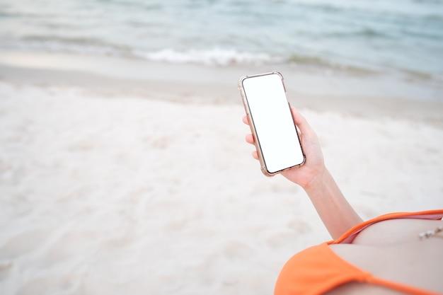 Mano de mujer sosteniendo teléfono móvil con maqueta de pantalla en blanco en la playa