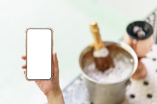 Mano de mujer sosteniendo el teléfono móvil de pantalla blanca en blanco con botella de champán en el cubo de hielo y dos vasos cerca de la piscina jacuzzi.