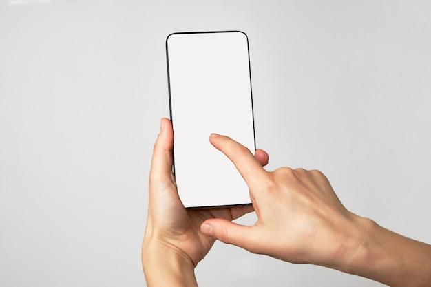 Mano de mujer sosteniendo el teléfono sobre fondo blanco con espacio de copia. mujer sosteniendo smartphone con pantalla en blanco.