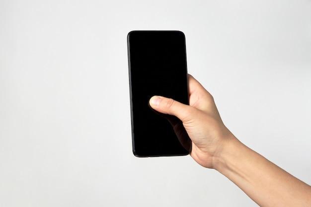 Mano de mujer sosteniendo el teléfono sobre fondo blanco con espacio de copia