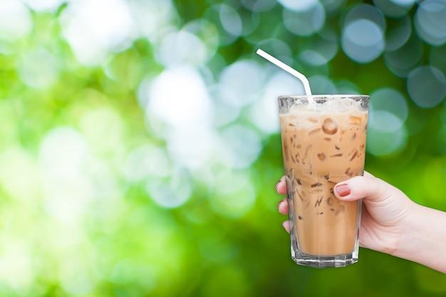 Mano de mujer sosteniendo el vaso de café helado sobre fondo verde de la naturaleza, café con leche helado