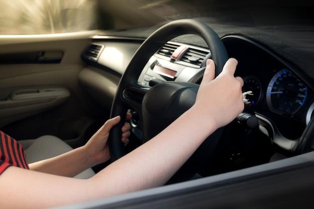 Mano de mujer sosteniendo el volante negro