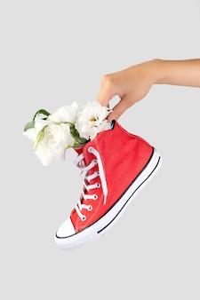 Mano de mujer sosteniendo una zapatilla roja de moda con flores