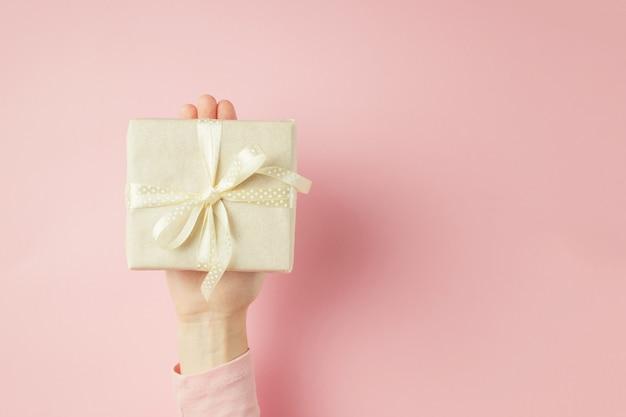 La mano de la mujer sostiene la caja de regalo en la palma en fondo rosado con el espacio de la copia