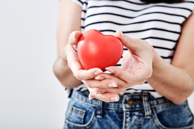 Mano de mujer sostiene un corazón rojo