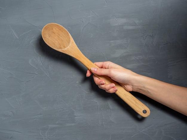 La mano de una mujer sostiene una cuchara de madera grande sobre un fondo de textura gris. herramientas para cocinar alimentos.