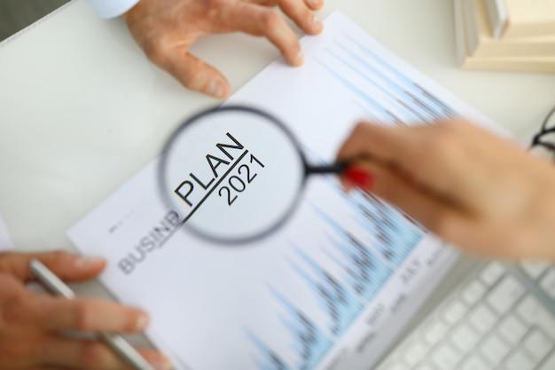 Mano de mujer sostiene lupa sobre plan de negocios para 2021