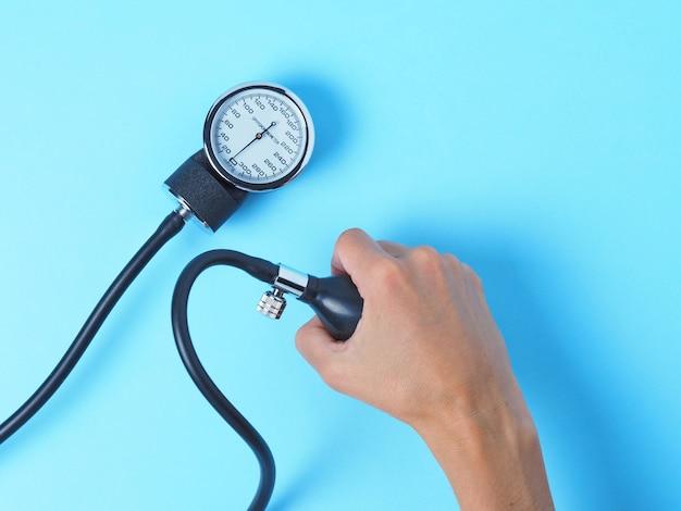 La mano de una mujer sostiene un monitor de presión arterial que muestra la presión arterial.