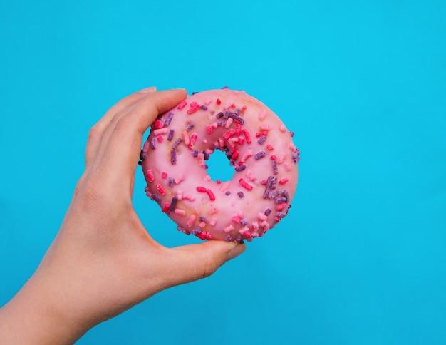 La mano de una mujer sostiene una rosquilla rosa sobre un fondo azul. productos de confitería. comida rápida nociva. la rosquilla está cubierta con glaseado y decorada con decoración comestible.
