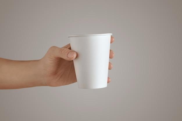 Mano de mujer sostiene la vista lateral de vidrio de papel para llevar vacío en blanco, aislado, irreconocible