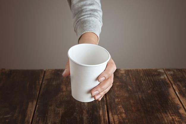 La mano de la mujer sostiene la vista superior del vidrio de papel para llevar vacío en blanco, sobre la mesa de madera cepillada envejecida vintage. aislado, irreconocible
